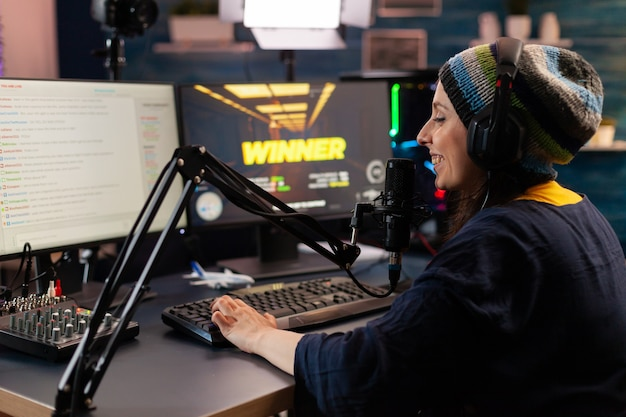 Game over für mann-streamer, der ein online-shooter-spiel mit modernem headseat und joystick spielt. cyber performt auf einem leistungsstarken pc und spricht mit spielern im chat, der während des professionellen wettbewerbs geöffnet ist