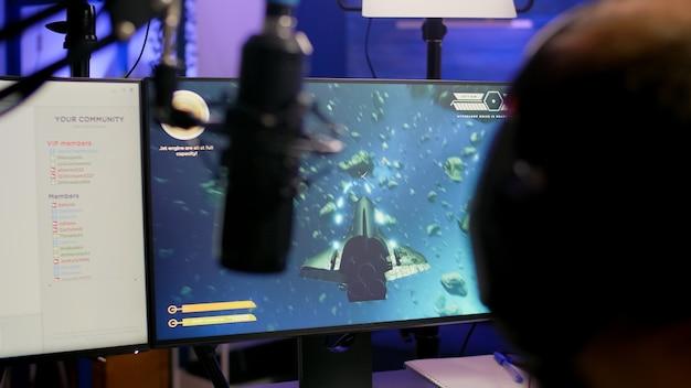 Game over für pro-streamer, der online-videospiel-space-shooter im streaming-raum mit modernem headseat spielt