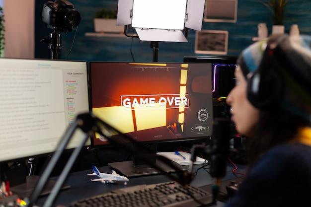 Game over für streamer, die mit anderen spielern über streaming-chat mit kopfhörern in das mikrofon sprechen. online-cyber-performer während eines gaming-turniers mit einem leistungsstarken pc mit rgb