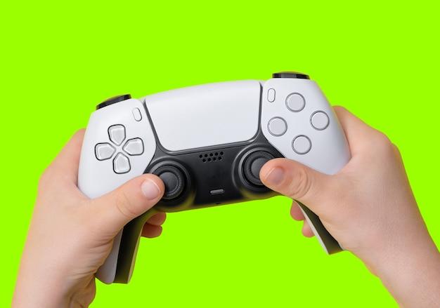 Gamecontroller auf kinderhand mit grünem hintergrund zum zuschneiden