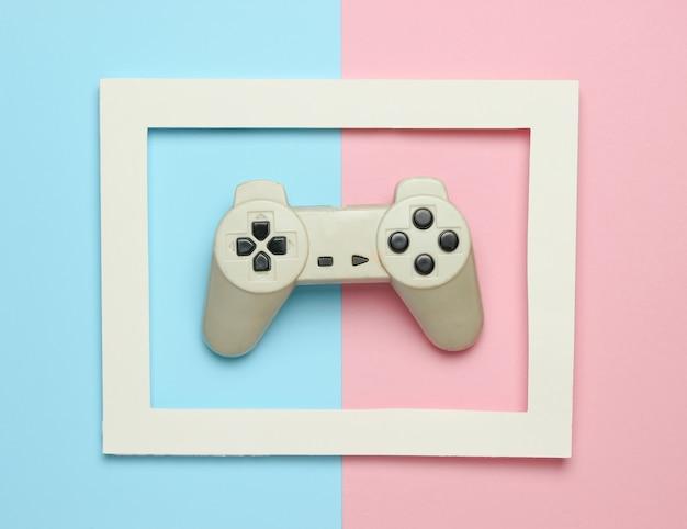 Gamepad in einem weißen rahmen auf einem farbigen hintergrund. draufsicht, minimalismus.