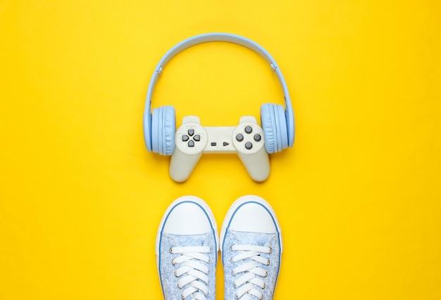 Gamepad mit kopfhörern, turnschuhen auf gelbem hintergrund