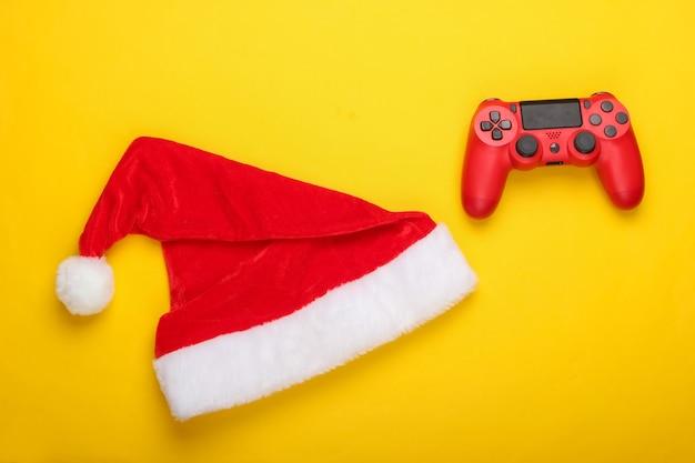 Gamepad mit weihnachtsmütze auf einem gelben
