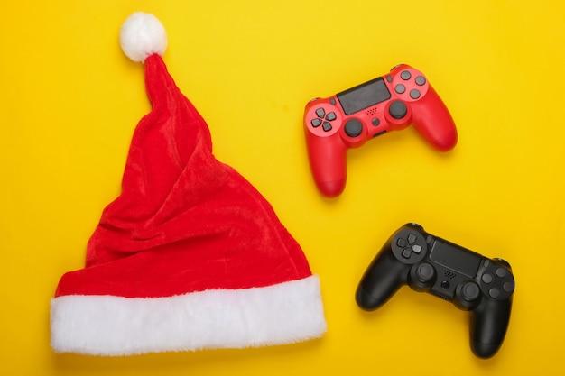 Gamepads mit weihnachtsmütze auf einem gelben