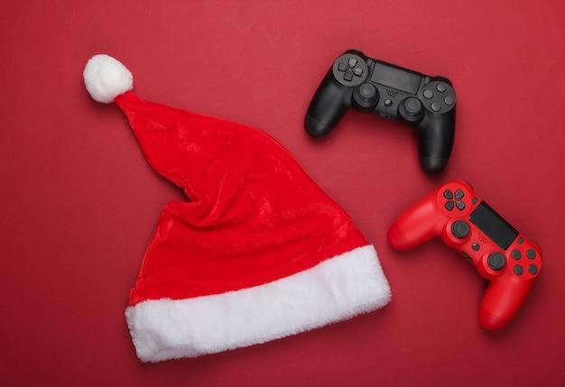 Gamepads mit weihnachtsmütze auf einem roten
