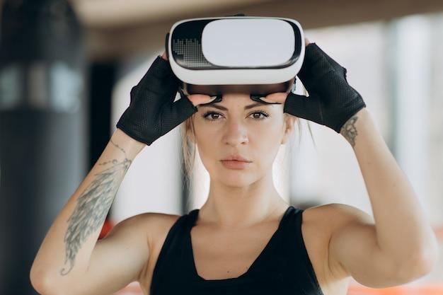 Gamer trägt eine brille mit erweiterter realität, die in der boxposition steht und action-simulator-spiel-mobile-app spielt