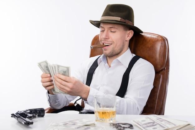 Gangster, der an einem tisch sitzt und geld zählt.