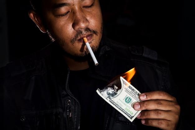 Gangster, der die dollarbanknote beleuchtet seinen zigarettentabak verwendet