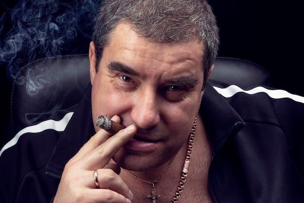 Gangster, ein zigarrenrauchender männlicher verbrecher, schaut wütend in die kamera und grinst