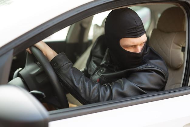 Gangster in einer schwarzen maske stiehlt das auto eines anderen