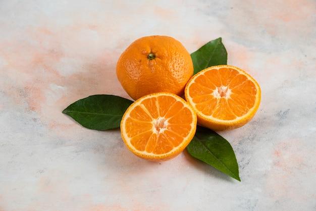 Ganz und halb geschnittene clementinenmandarinen mit blättern über bunter oberfläche