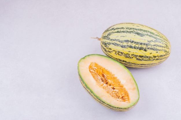 Ganz und halb geschnittene melone in grauer oberfläche