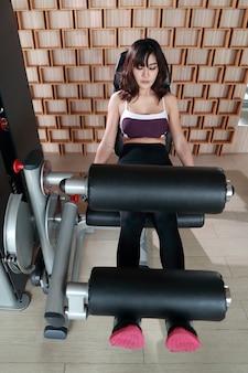Ganzaufnahme der jungen gesunden asiatischen frau, die übungsmaschine in der turnhalle verwendet