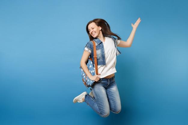 Ganzaufnahme der jungen glücklichen lachenden studentin in denimkleidung mit rucksackspringen, die hände einzeln auf blauem hintergrund ausbreiten. ausbildung an der universität. kopieren sie platz für werbung.