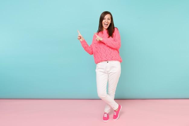 Ganzaufnahme der lächelnden jungen frau in gestricktem rosenpullover, weiße hose posiert