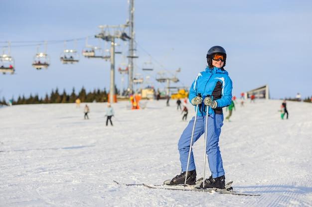 Ganzaufnahme des frauenskifahrers stehend auf einer skisteigung