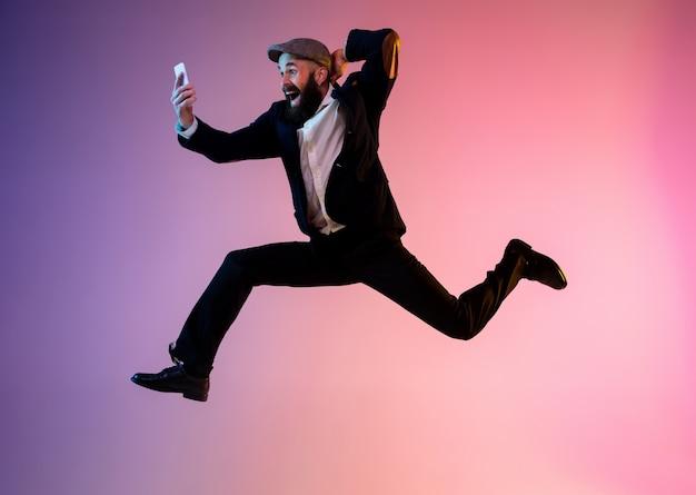 Ganzaufnahme des glücklichen springenden mannes in neonlicht und farbverlauf