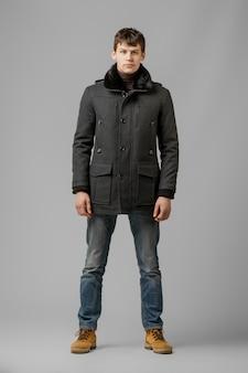 Ganzaufnahme des gutaussehenden mannes im warmen mantel, der im studio aufwirft