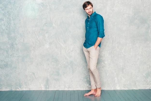 Ganzaufnahme des hübschen selbstbewussten hipster-lumbersexual-geschäftsmannmodells, das lässige jeanshemdkleidung trägt.