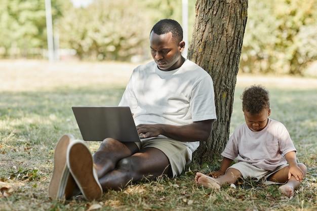Ganzaufnahme des jungen afroamerikanischen mannes, der draußen im park laptop mit süßem babysohn benutzt