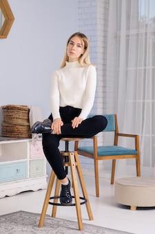 Ganzaufnahme des jungen mädchens sitzend auf stuhl im wohnzimmer