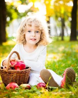 Ganzaufnahme des kindes mit korb mit roten äpfeln, die auf gelben blättern im herbstpark sitzen