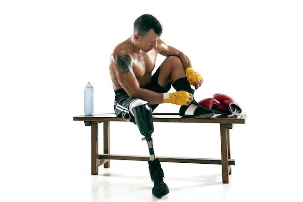 Ganzaufnahme des muskulösen sportlers mit beinprothese, kopienraum. männlicher boxer in handschuhen, der sich auf das üben vorbereitet. getrennt auf weißer wand. konzept des sports, gesunder lebensstil.