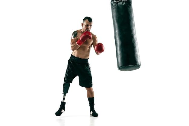 Ganzaufnahme des muskulösen sportlers mit beinprothese, kopienraum. männlicher boxer in roten handschuhen, der trainiert und übt. getrennt auf weißer wand. konzept des sports, gesunder lebensstil.