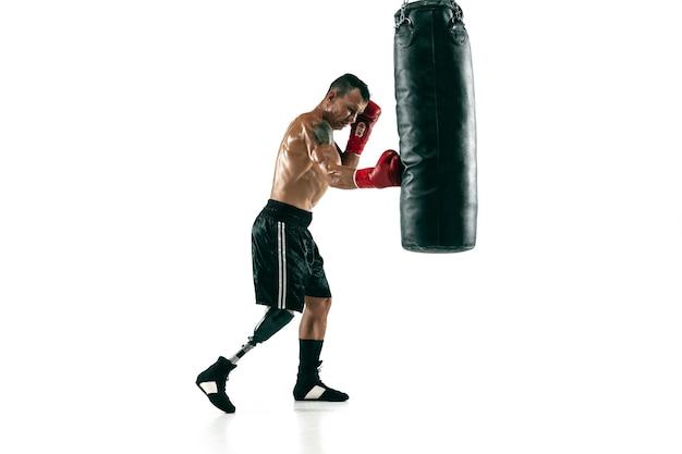 Ganzaufnahme des muskulösen sportlers mit beinprothese, kopienraum. männlicher boxer in roten handschuhen, die trainieren und üben. getrennt auf weißer wand. konzept des sports, gesunder lebensstil. Kostenlose Fotos