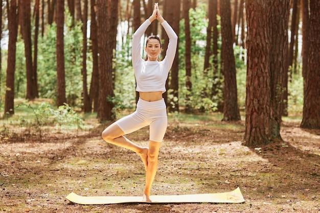 Ganzaufnahme einer attraktiven frau, die sportkleidung trägt, die auf karemat in yoga-pose steht