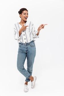 Ganzaufnahme einer attraktiven jungen afrikanischen frau, die isoliert über weißer wand steht und mit dem finger auf den kopierraum zeigt
