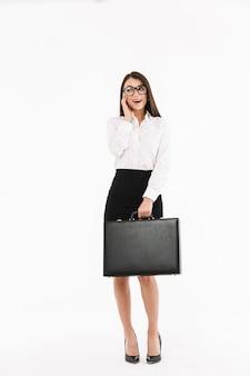 Ganzaufnahme einer attraktiven jungen geschäftsfrau in formeller kleidung, die isoliert über weißer wand steht und aktentasche trägt