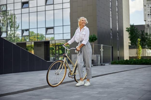 Ganzaufnahme einer attraktiven lächelnden frau mit fahrrad, die vor einem modernen geschäftszentrum steht