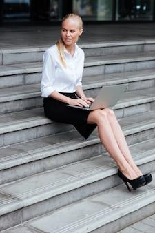 Ganzaufnahme einer blonden geschäftsfrau, die auf dem laptop tippt, während sie draußen auf der treppe sitzt