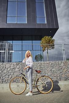Ganzaufnahme einer glücklich lächelnden kaukasischen frau, die aufhört, ihr fahrrad zu fahren, während sie vor einem modernen gebäude mit dem handy spricht