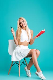 Ganzaufnahme einer glücklichen blonden frau, die ein notizbuch durchlöchert und auf einem stuhl sitzt, isoliert auf blauem hintergrund