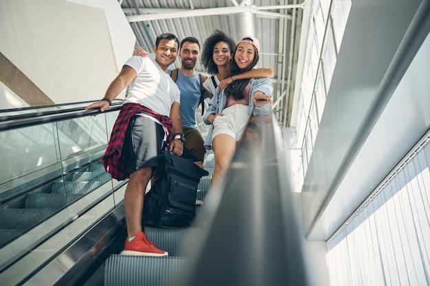 Ganzaufnahme einer glücklichen, freundlichen gruppe mit koffer, die auf der rolltreppe des internationalen flughafens steht