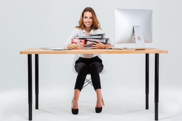 Ganzaufnahme einer glücklichen geschäftsfrau, die ordner hält, während sie am schreibtisch sitzt, isoliert auf weißem hintergrund