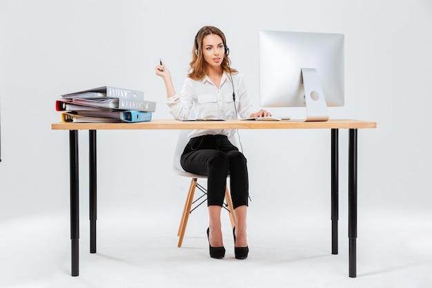 Ganzaufnahme einer glücklichen jungen frau, die mit computer im callcenter auf weißem hintergrund arbeitet