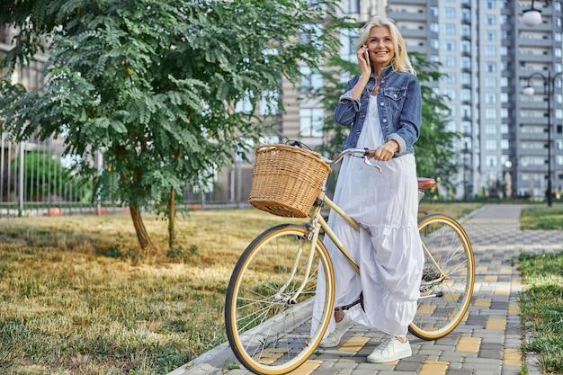 Ganzaufnahme einer glücklichen lächelnden frau im langen weißen kleid, die auf dem smartphone auf der straße spricht, isoliert auf modernem gebäudehintergrund