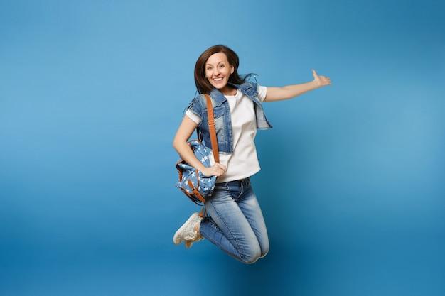 Ganzaufnahme einer jungen, fröhlichen, fröhlichen studentin in denim-kleidung mit rucksackspringen und ausbreitenden händen einzeln auf blauem hintergrund. ausbildung an der hochschule. kopieren sie platz für werbung.