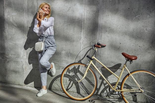 Ganzaufnahme einer lachenden frau, die in der nähe ihres fahrrads steht, während sie mit einem geschäftspartner auf dem handy spricht