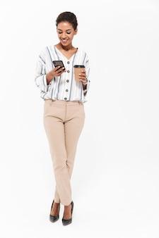 Ganzaufnahme einer lächelnden jungen afrikanischen geschäftsfrau, die isoliert über weißer wand steht, kaffee zum mitnehmen trinkt und handy benutzt