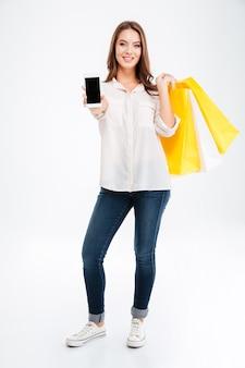 Ganzaufnahme einer lächelnden jungen frau, die ein smartphone mit leerem bildschirm zeigt und taschen isoliert auf einer weißen wand hält