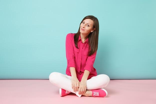 Ganzaufnahme einer lächelnden jungen frau in rosa hemdbluse, weiße hose auf dem boden sitzend