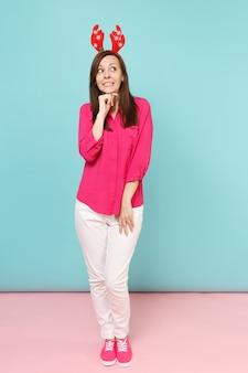 Ganzaufnahme einer lustigen jungen frau in rosa hemdbluse, weißen hosen, hirschhörnern, die einzeln auf hellrosa blauer pastellwand posieren.