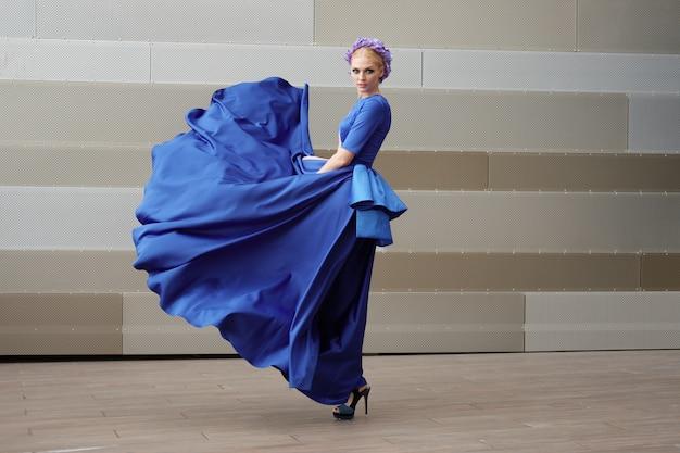 Ganzaufnahme einer modefrau mit ihrem kleiderfliegen in der luft