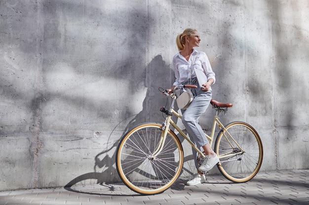 Ganzaufnahme einer modischen frau in business-freizeitkleidung, die ihre hände am lenker eines city-bikes hält, isoliert an der grauen wand