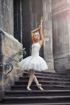 Ganzaufnahme einer schönen jungen balletttänzerin, die anmutig auf der treppe eines alten gebäudes in der stadt posiert.
