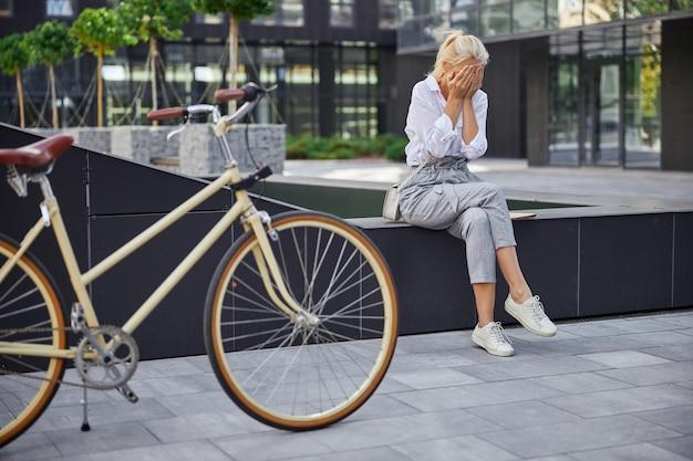 Ganzaufnahme einer stilvollen frau, die im freien weint, während sie im modernen stadtpark hinter ihrem fahrrad sitzt